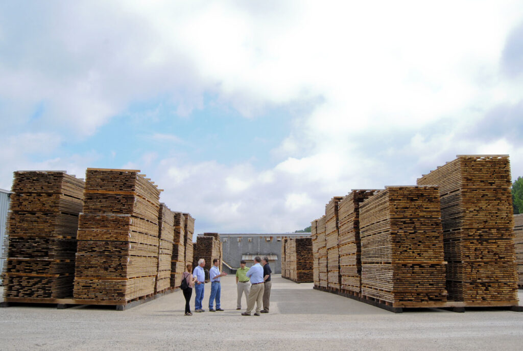 A group of people stand outside in front of several stacks of lumber at powell valley millwork.