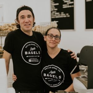 Katie and Michael of Native Bagel Company stand next to each other inside their bagel shop in eastern kentucky