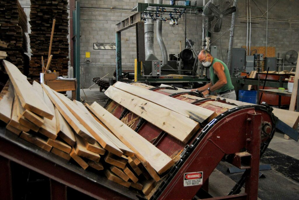 A man in a mask loads lumber onto a conveyer belt at powell valley millwork in eastern kentucky.