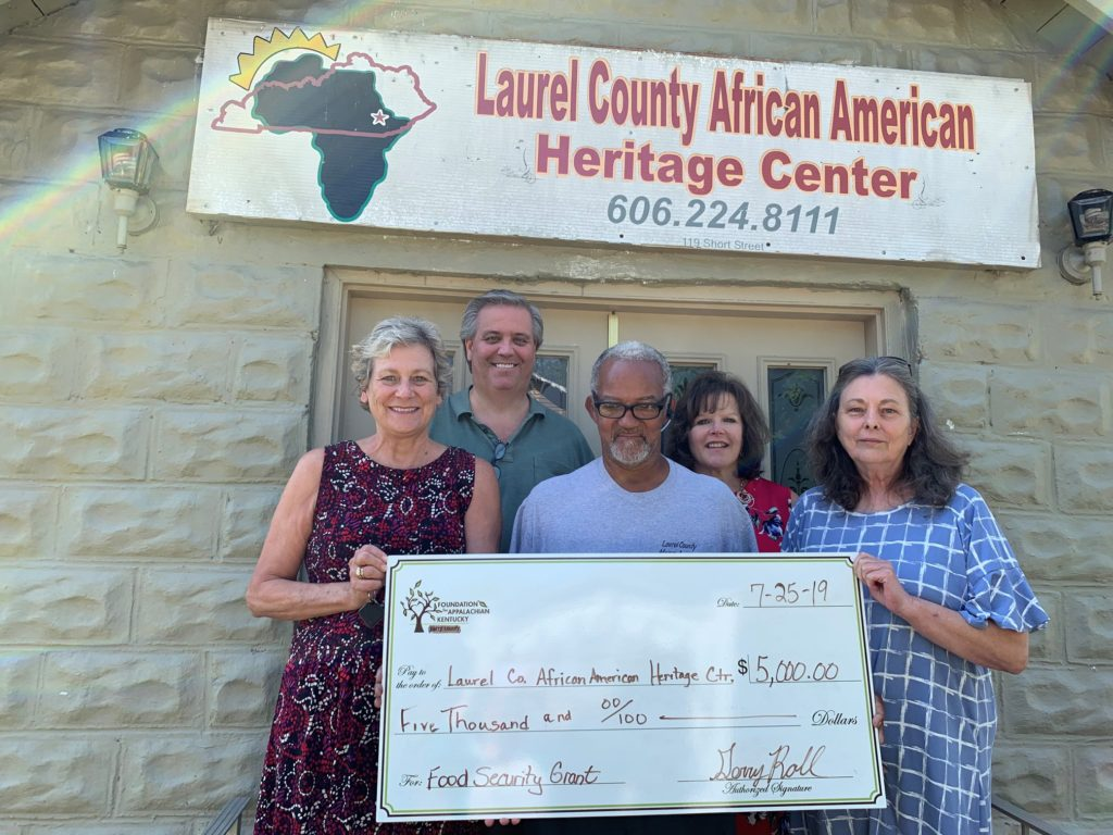 A group stands with a big check in front of Laurel County African American heritage center in eastern kentucky.