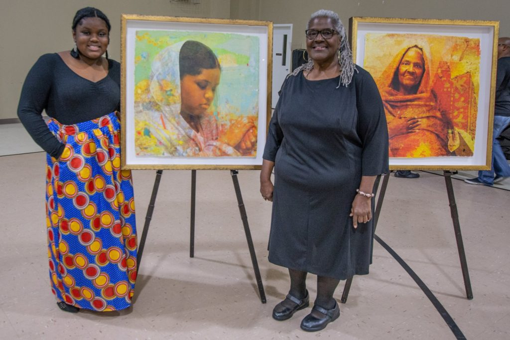 Two women pose with Winchester Kentucky portraits as part of the I was here exhibit, racial equity work by clark county residents