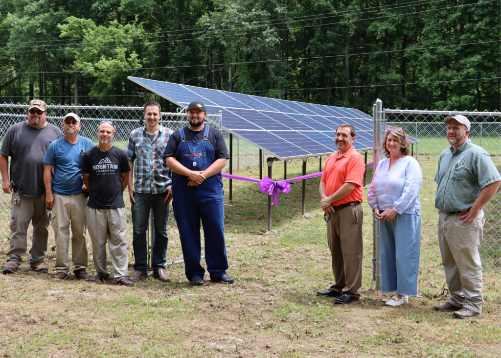 SEveral people stand in front of solar panels at buckhorn nonprofit.