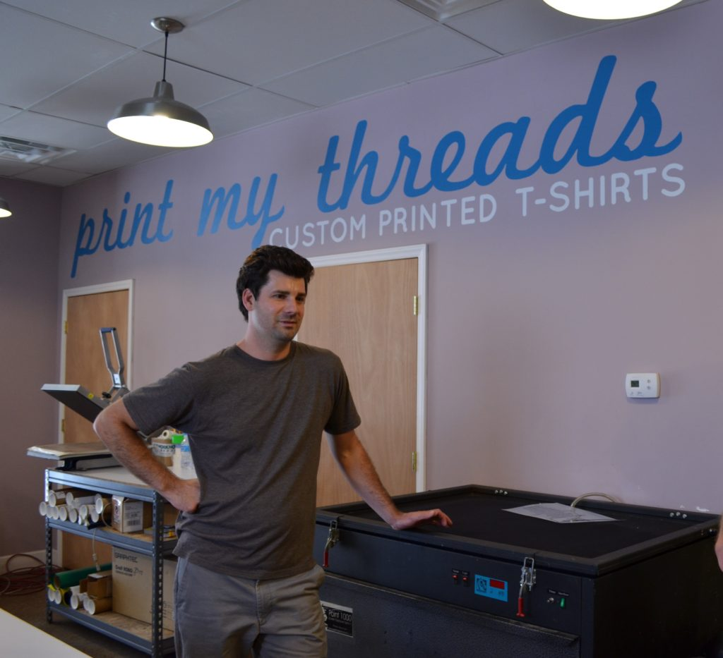 The owner of Print My Threads, a business in eastern kentucky, leans on a piece of screen printing equipment.