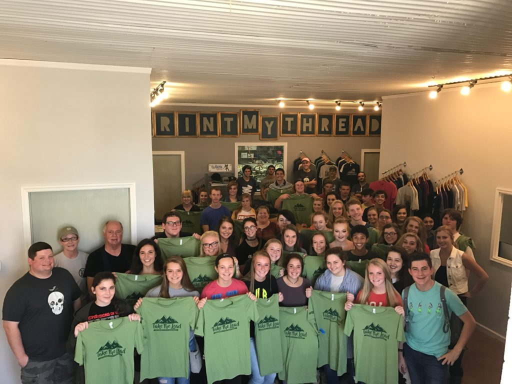 High school students stand with their tshirts inside Print My Threads. The leadership program recently toured the Eastern Kentucky facility