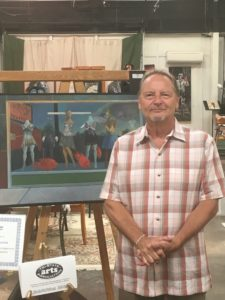 Dan click poses in front of an easel inside grayson art gallery in carter county, kentucky.