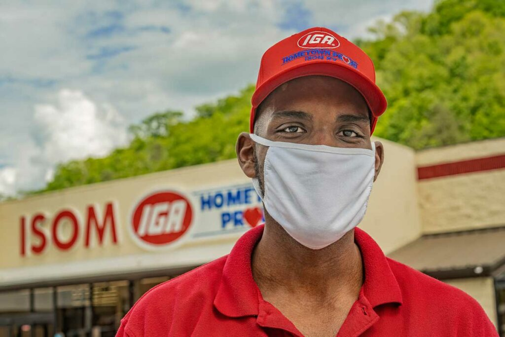 A man in a red shirt and white face mask stands in front of ISOM IGA during covid-19 in eastern kentucky.