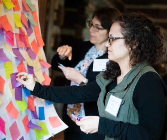 women using sticky notes to brainstorm