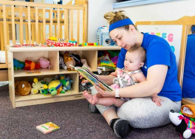 Employee holds a child while reading a book. The Hazard childcare facility helps with Eastern Kentucky childcare deserts