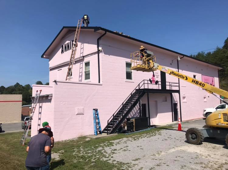 A lift takes solar panels on top of the pink building at Annie's Frugal Finery in Whitesburg. The Eastern Kentucky business is also energy efficient