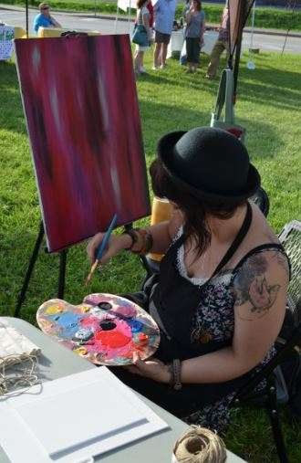 artist painting a red canvas at an event in hazard called thursdays on the triangle.