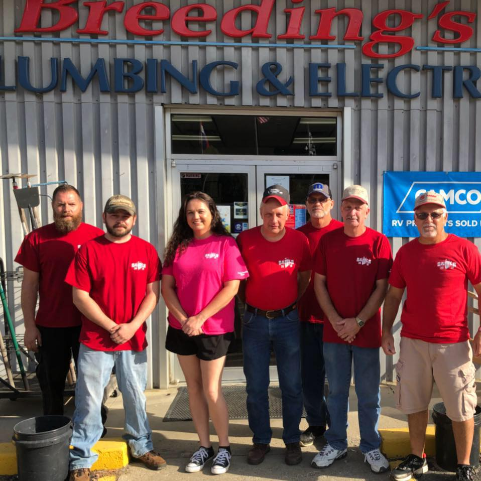 The staff at Breeding's Plumbing and Electric in Letcher County, Kentucky, stand in front of the store, which is now solar powered.