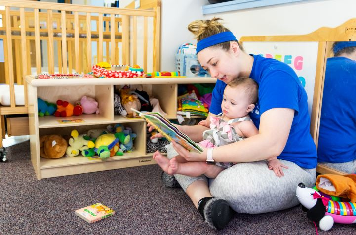 childcare provider holds and reads to a baby at new beginnings in hazard, kentucky.
