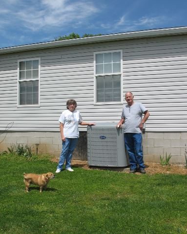 Two people stand with heating and cooling equipment during an energy efficiency assessment of their home in East Kentucky.