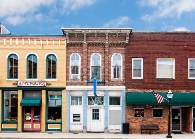 Three buildings on main street in Eastern Kentucky. Open sign hands in a door. MACED is offering economic recovery loans for COVID-19.