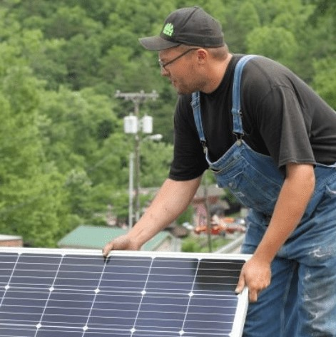 Man holds solar panel on top of a roof in the mountains of Eastern Kentucky.