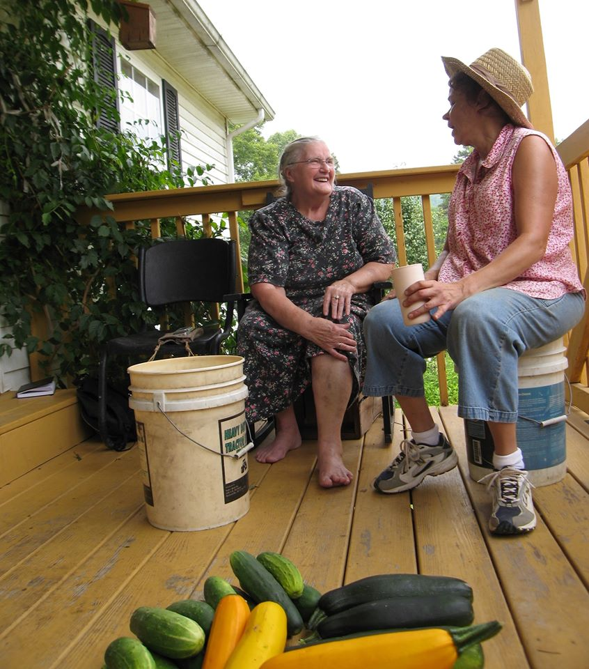 Two women talk on a porch about the Grow Appalachia program that helps Eastern Kentucky families garden and grow food
