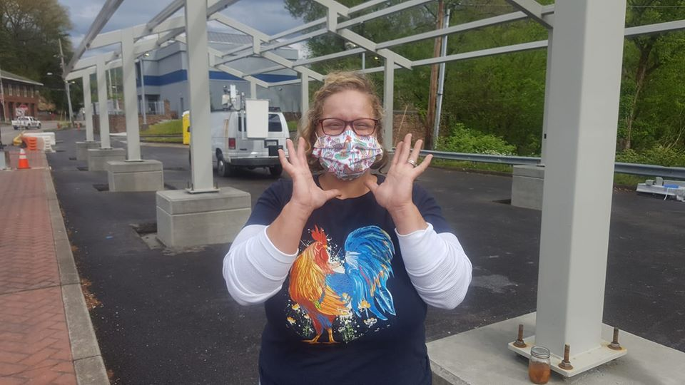 A woman in mask stands in front of the he Perry County Farmers Market pavilion currently under construction in Hazard, Kentucky.