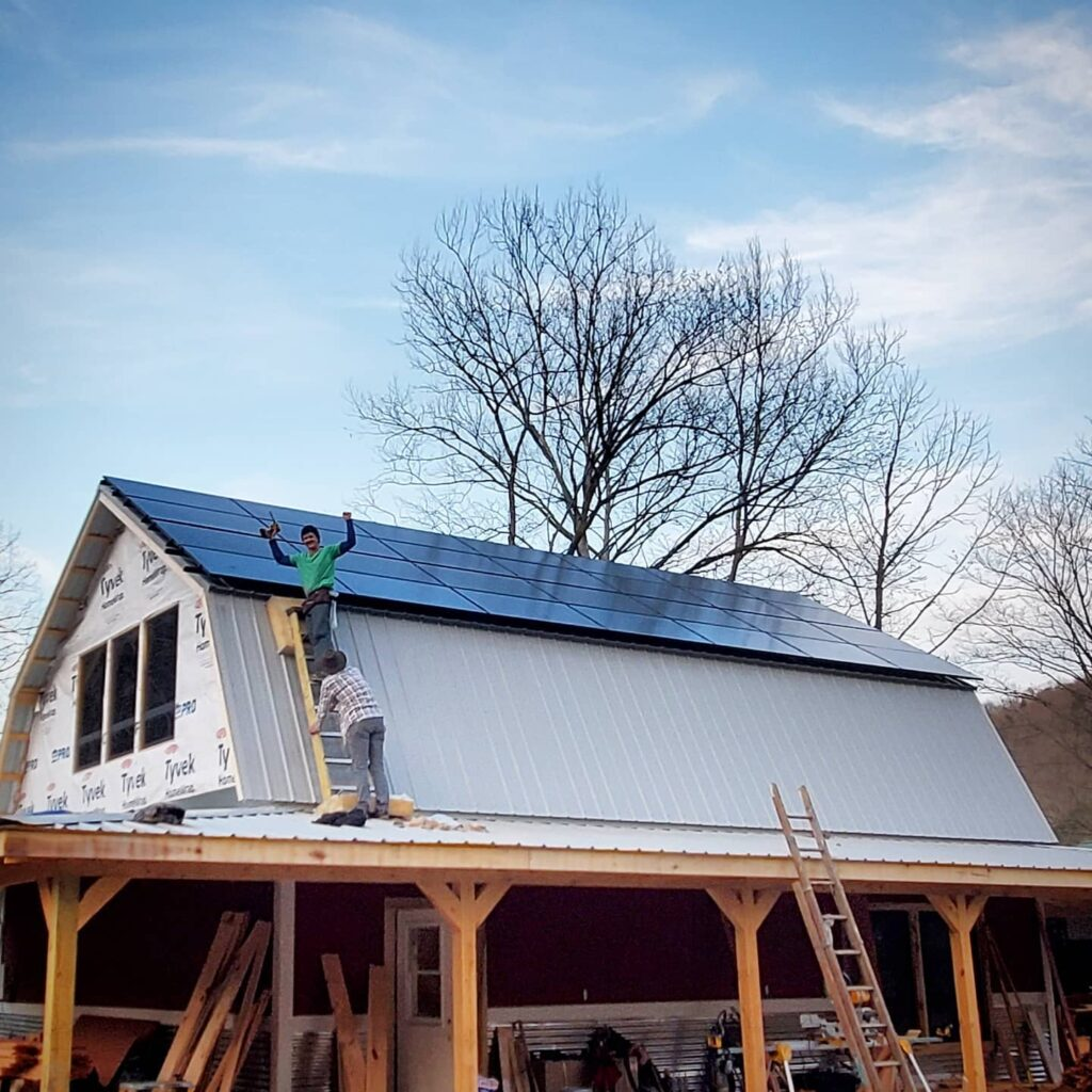 Ben Tatum stands on a ladder in front of a building with solar panels on it after finishing homegrown hideaways solar project.