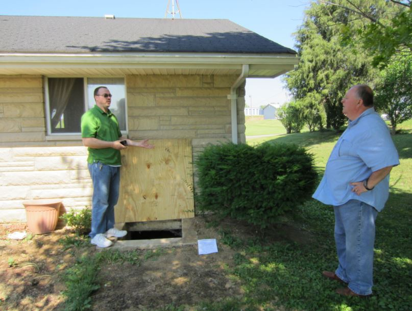 Two men stand during an energy efficiency assessment of a home in Eastern Kentucky.