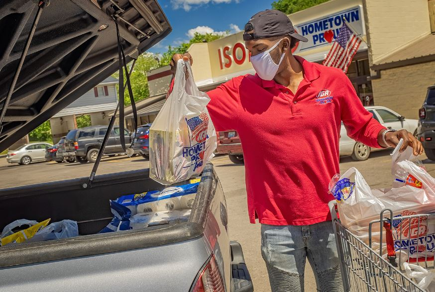 Employee wears masks while loading bagged groceries into the back of a truck during covid-19 in eastern kentucky.