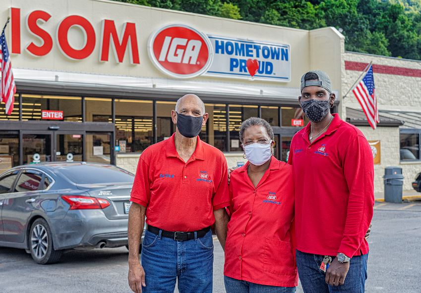 Three people stand in front of isom iga, a grocery store in rural letcher county, kentucky. Each are wearing masks.