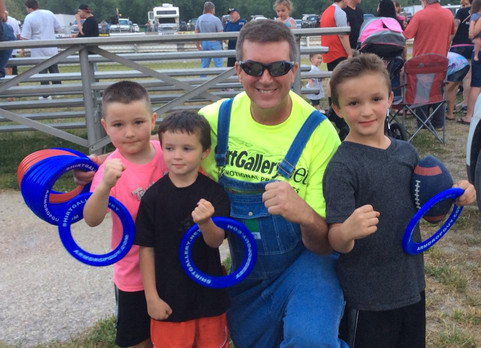 Kent Rose with three kids at a car racing event in Eastern Kentucky. His legacy continues with scholarships and other kids programming.