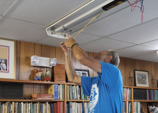 Person installs LED lighting for a nonprofit