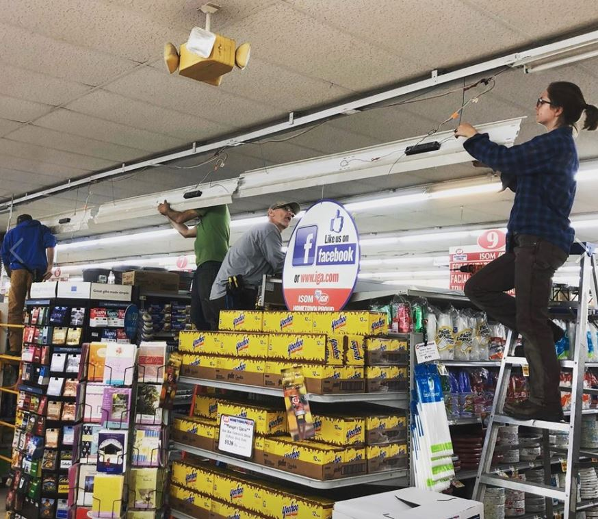 Four people stand on ladders inside of a grocery store. They are installing new energy efficiency LED lights in Isom IGA.