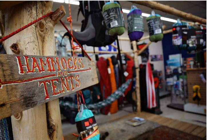 A handmade sign reads hammocks and tents. The sign hangs inside the store in Richmond, Kentucky.