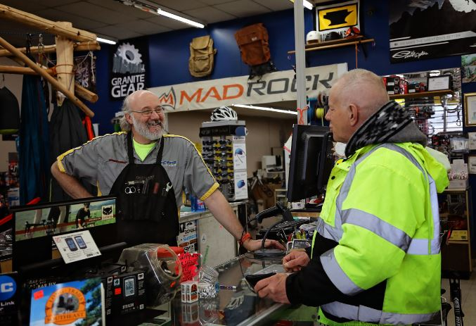 Mike stands at the cash register with a customer inside his outdoor store in Richmond, Kentucky.