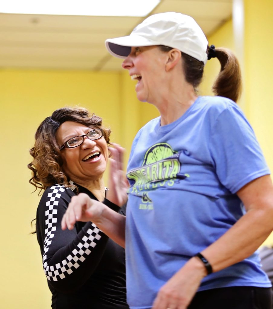 Two women high five at a fitness class in hazard, kentucky. This project is supported by the mountain association's business support.