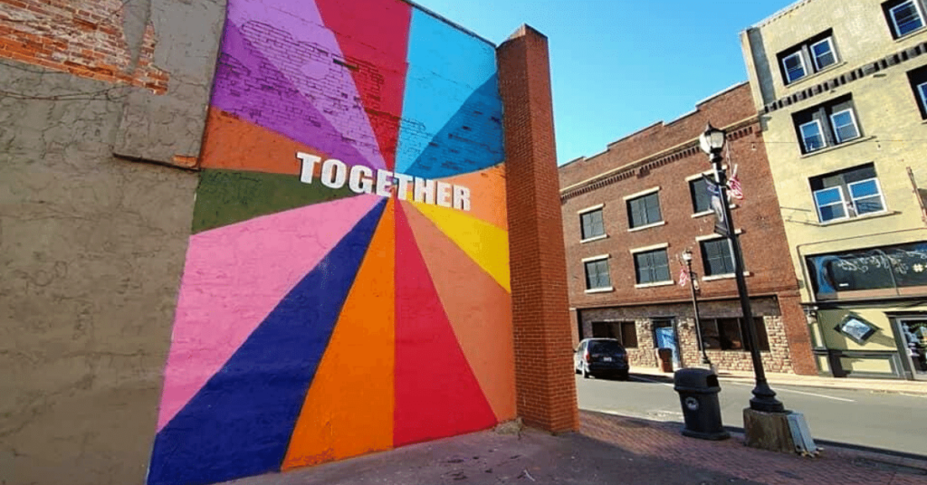 The word together is painted on a wall downtown Hazard in the middle of several colorful swatches.