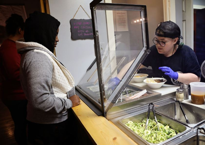 Employee serves noodles at Noodle Nirvana, a Berea, Kentucky, social enterprise restaurant. Hole and Corner uses the same space