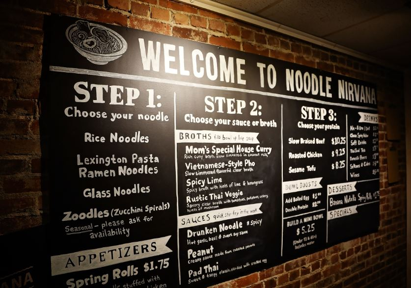 The menu board against a brick wall at Noodle Nirvana. MACED supports the business with a loan and technical assistance