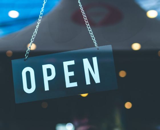 Open sign hangs in a door. MACED is offering economic recovery loans in Eastern Kentucky to help businesses during COVID-19.
