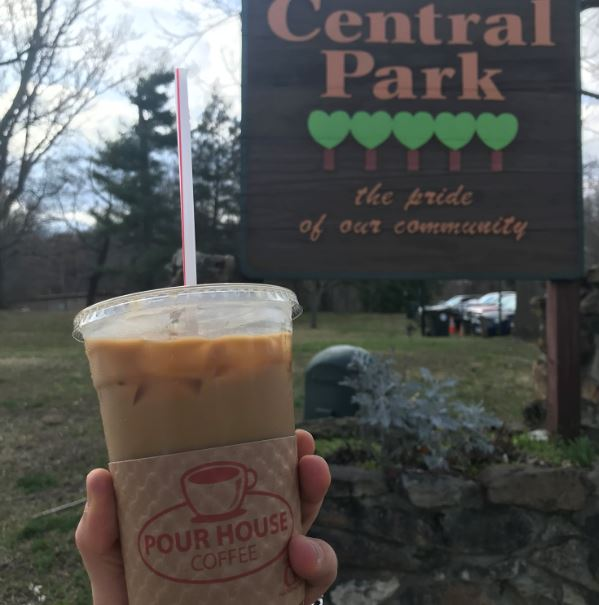Person holds a cold brew coffee from Pour house coffee in Ashland, Kentucky, adjacent to Ashland's beautiful Central Park.