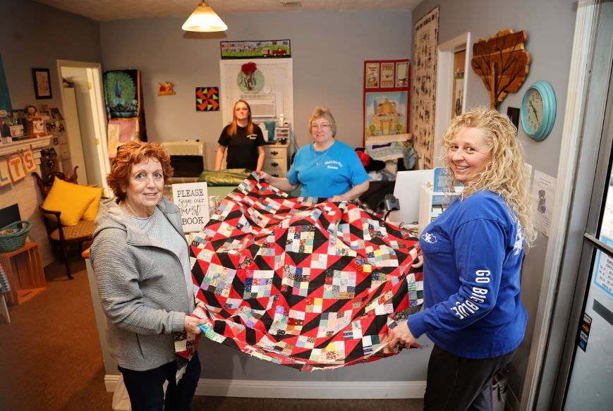 A group of women stand with a quilt and fabric inside the shop in Stanton, Kentucky, in Powell County.