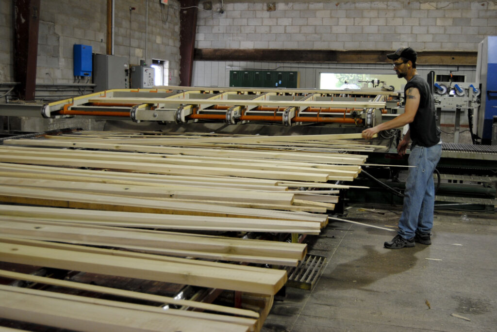A man stands in front of several pieces of wood at powell Valley millwork.