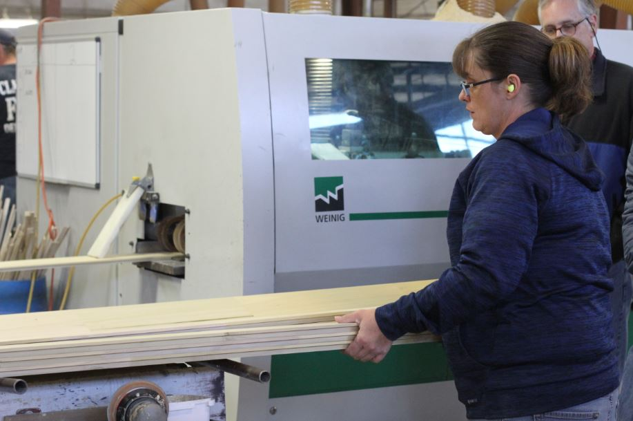 An employee at Powell Valley Millwork inspects a piece of wood. MACED provides business financing to the EKY family owned business