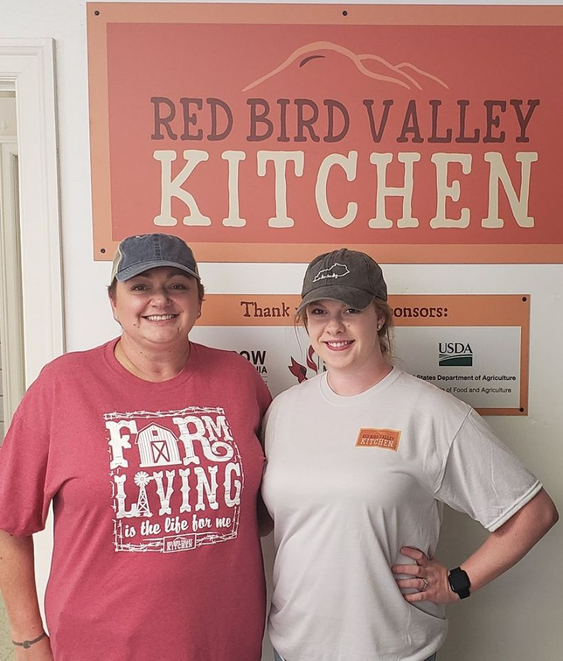 Two volunteers stand in front of a sign for Red Bird Mission's Red Bird Valley kitchen. Community members can use the kitchen to put up food.