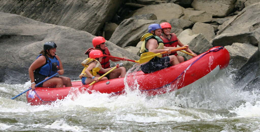 several people inside a raft going down the river at sheltowee trace adventure resort