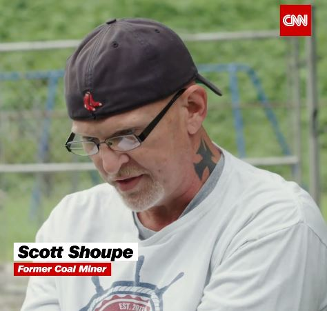 Scott sits in an interview with CNN about his experience being a coal miner who transitioned to energy efficient and renewable energy