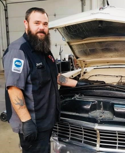 An employee at SEcond Chance Auto in Louisa, Kentucky works on a vehicle with its hood up. Addiction recovery Care started the shop.