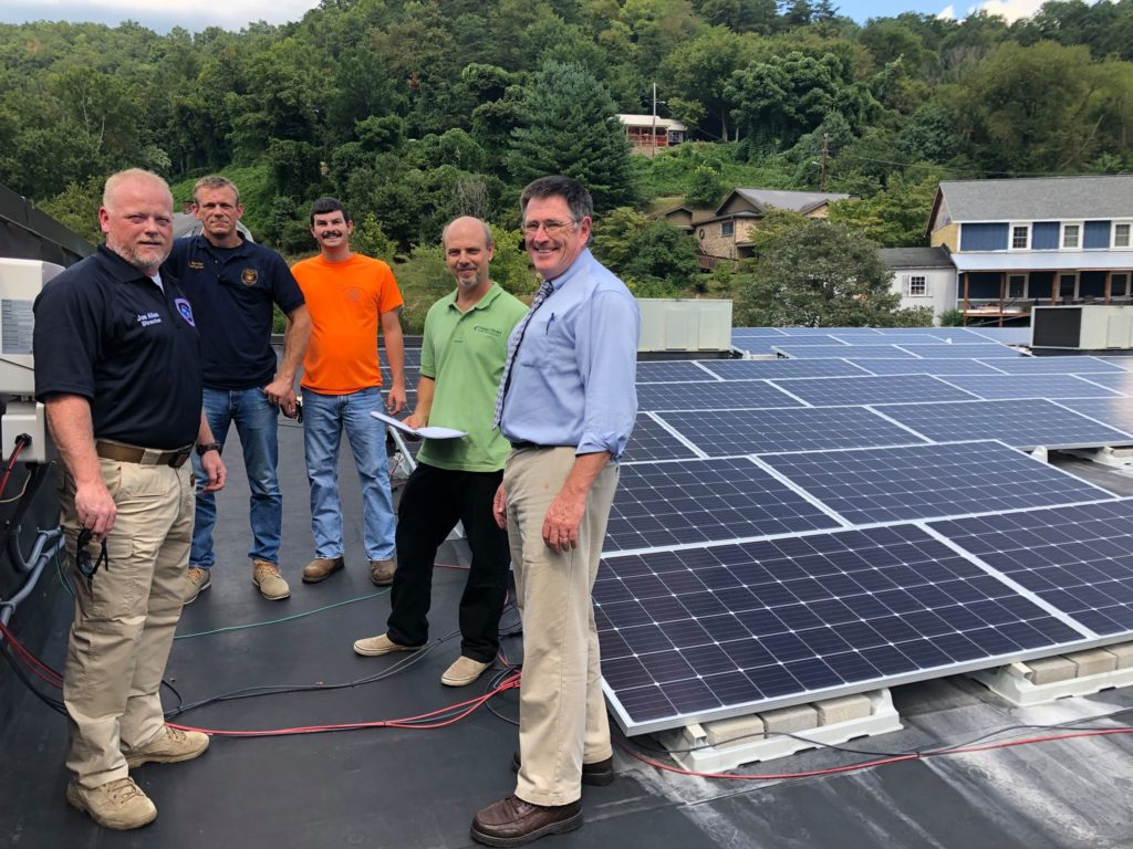 First responders in Eastern Kentucky are shown on a roof learning about how to respond to a building with solar panels.