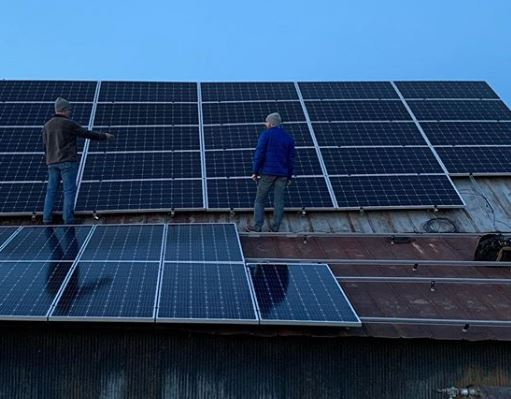 Solar being installed by two men on the Lazy Eight Stock Farm roof in Paint Lick, Kentucky.