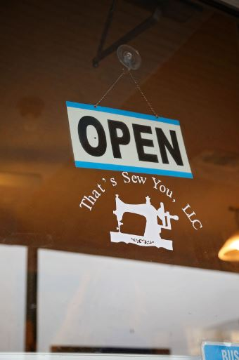 The decal on the window of That's Sew You quilt shop in Stanton, Kentucky. The shop is supported by MACED's business financing