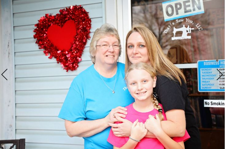 Susan Watson stands with her family in front of That's Sew You quilt shop in Stanton, Kentucky. MACED provides them a business loan