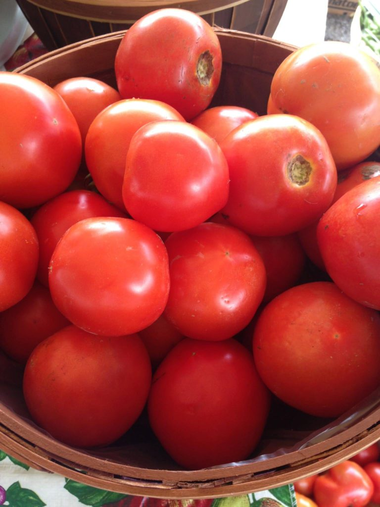 a bunch of tomatoes in a bowl at a farmers market in eastern kentucky. maced supports farmers with loans and energy assistance