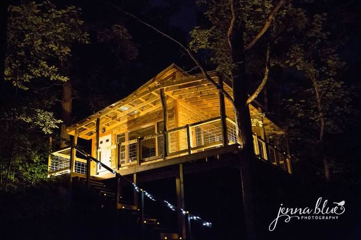 The treetop flyer, which is a treehouse, is lit up at night at homegrown hideaways in berea, kentucky.