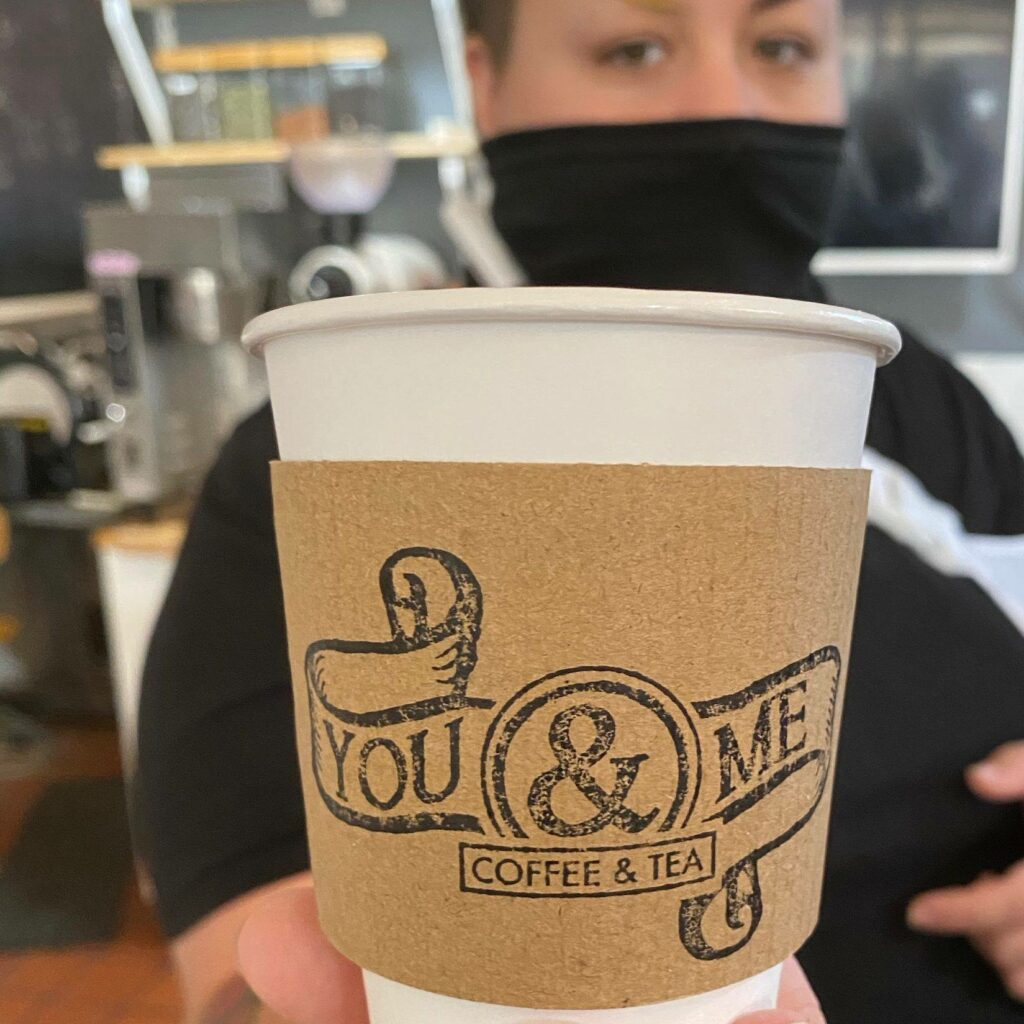 An employee wearing a mask holds a You & Me Coffee & Tea cup in corbin, kentucky.